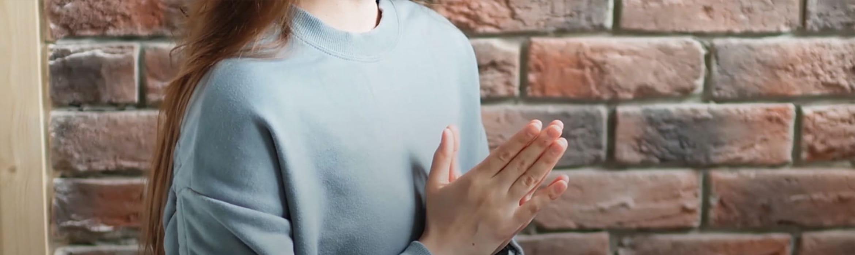 Žena sedí se sepnutýma rukama