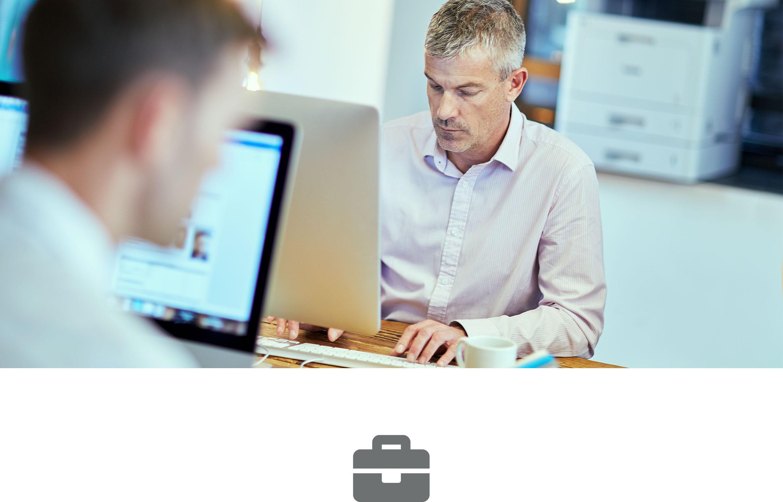 Dva muži sedí u stolu a pracují na počítačích s laserovou tiskárnou v pozadí