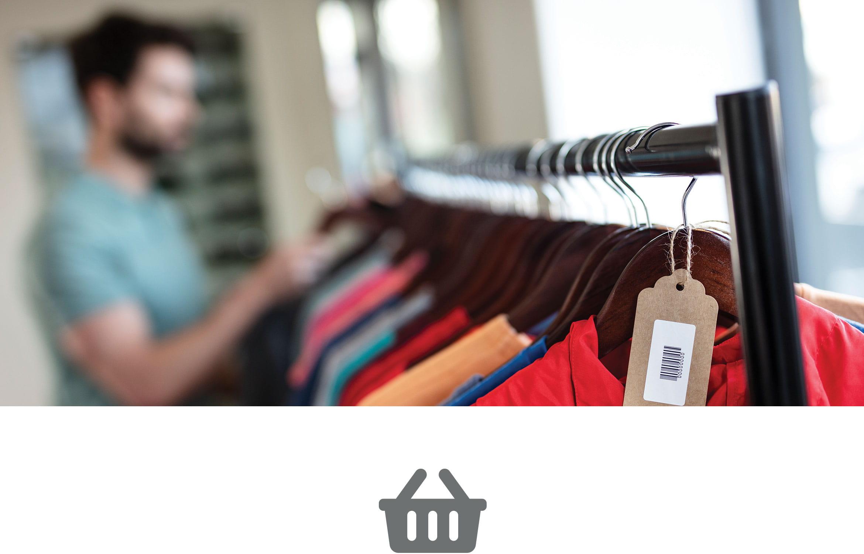 Muž prohlíží šaty v obchodě s oděvy, dole šedá ikona nákupního košíku