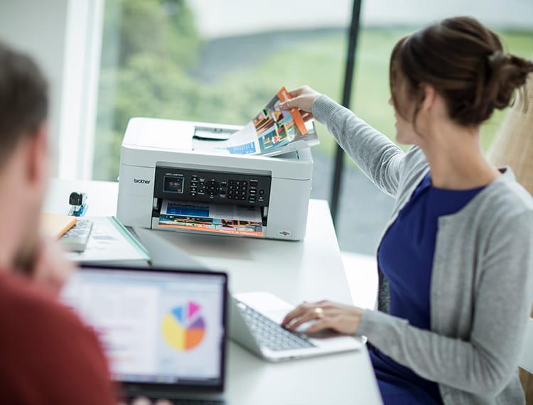 žena v domácí kanceláři stojí vedle tiskárny