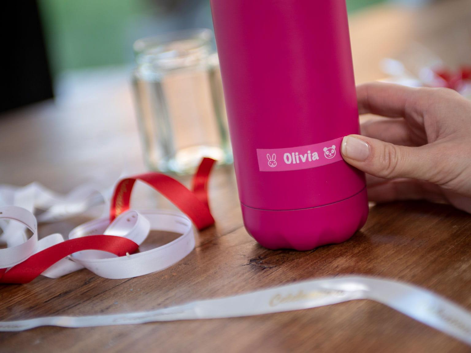 Brother růžový štítek na růžové láhvi s bílými a červenými stužkami
