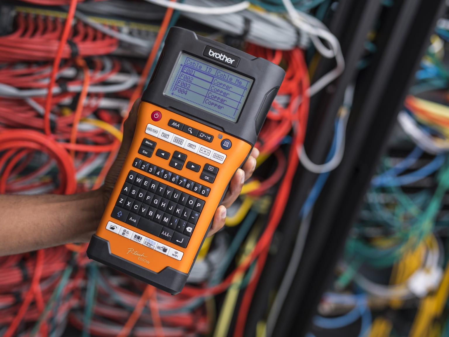 Tiskárna štítků PT-E550W držená v ruce, před síťovými kabely