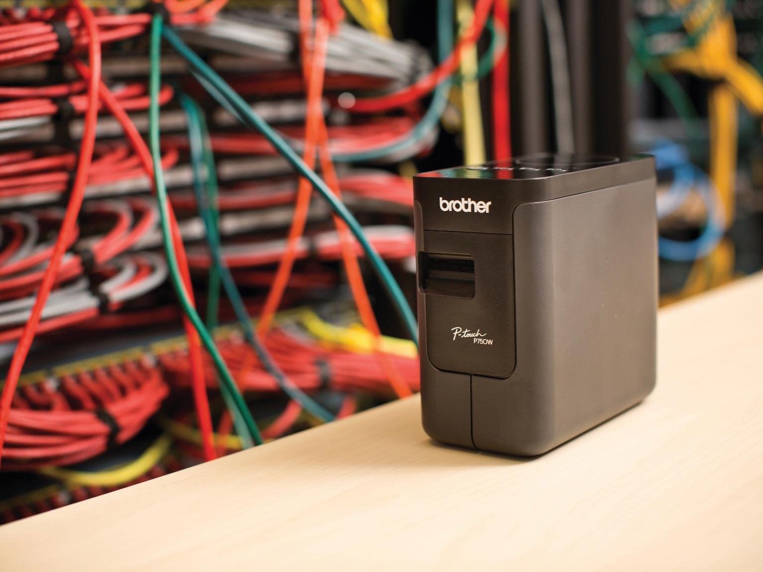 Tiskárna štítků Brother PT-P750TDI na stole před síťovými kabely