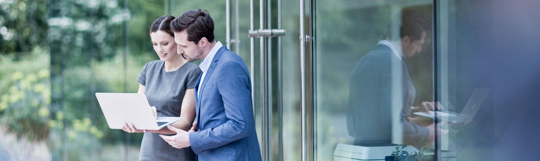 Muž s tmavými vlas v modrém obleku s bílou košilí mluví s ženou v šedých šatech s notebookem, skleněné dveře, uvnitř tiskárny, zelené keře
