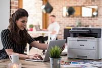 Sedící žena s multifunkční tiskárnou na stole