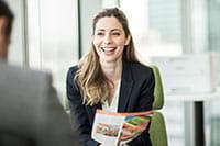 Usmívající se žena sedí v kanceláři s barevnou tiskárnou v pozadí