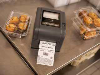 Tiskárna štítků Brother TD-4T na ocelovém stole vedle dortů v pekárně