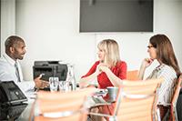 2 ženy a muž sedící kolem stolu