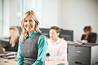 Žena v kanceláři s laserovou tiskárnou v pozadí