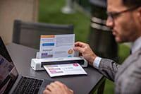 Muž s brýlemi, pomocí přenosného počítače a přenosného skeneru dokumentů Brother DS740D skenuje dokumentem A4