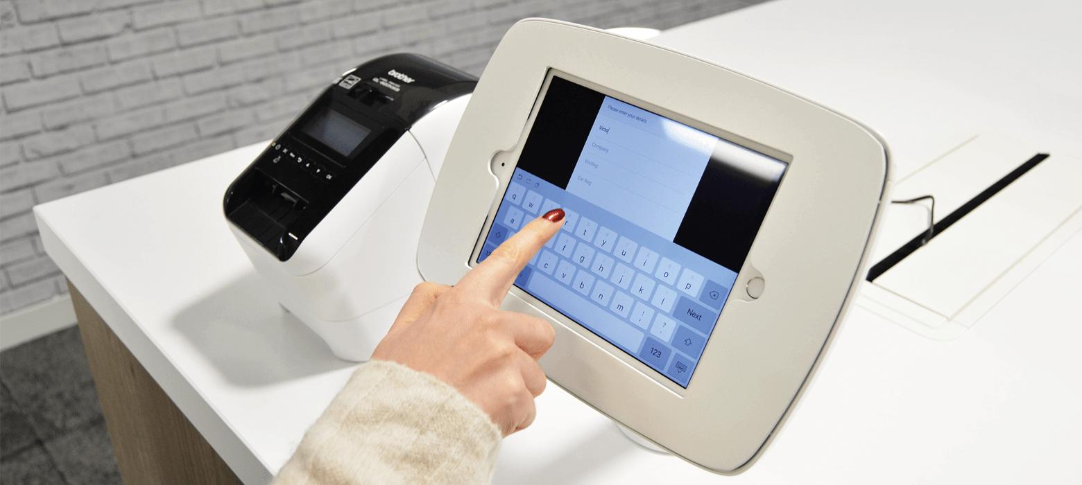 Žena zadává informací přihlášení návštěvníka na dotykovém displeji